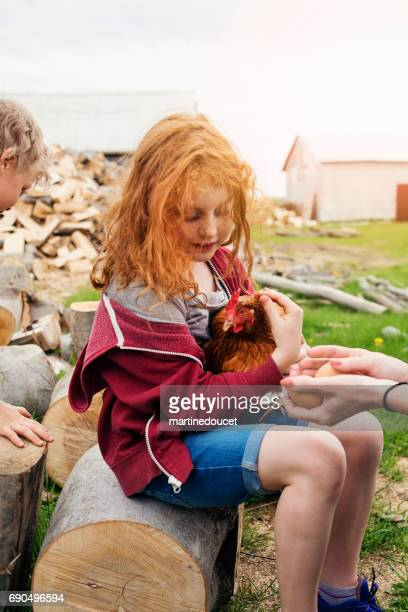 Redhead little girl tenderly holding a hen with eggs.