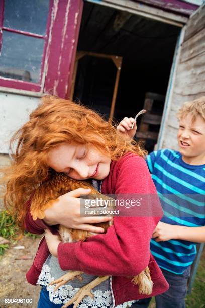 Redhead little girl tenderly holding and hugging a hen.