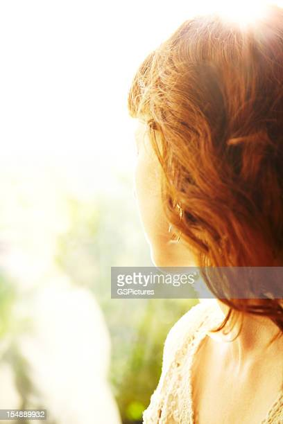 Redhead woman backlit by sun looking out to nature