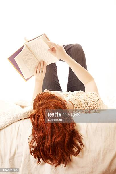 Redhead woman lying in bed reading
