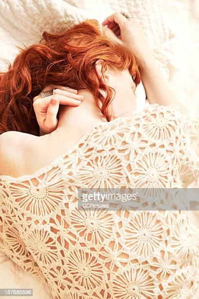 Rotes Haar-Frau liegen im Bett mit Gesicht verdeckt
