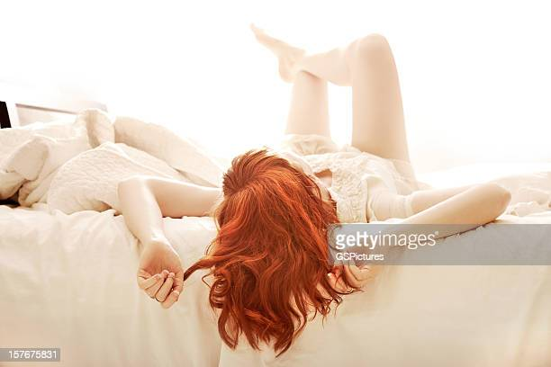 Redhead woman lying in bed with her feet up