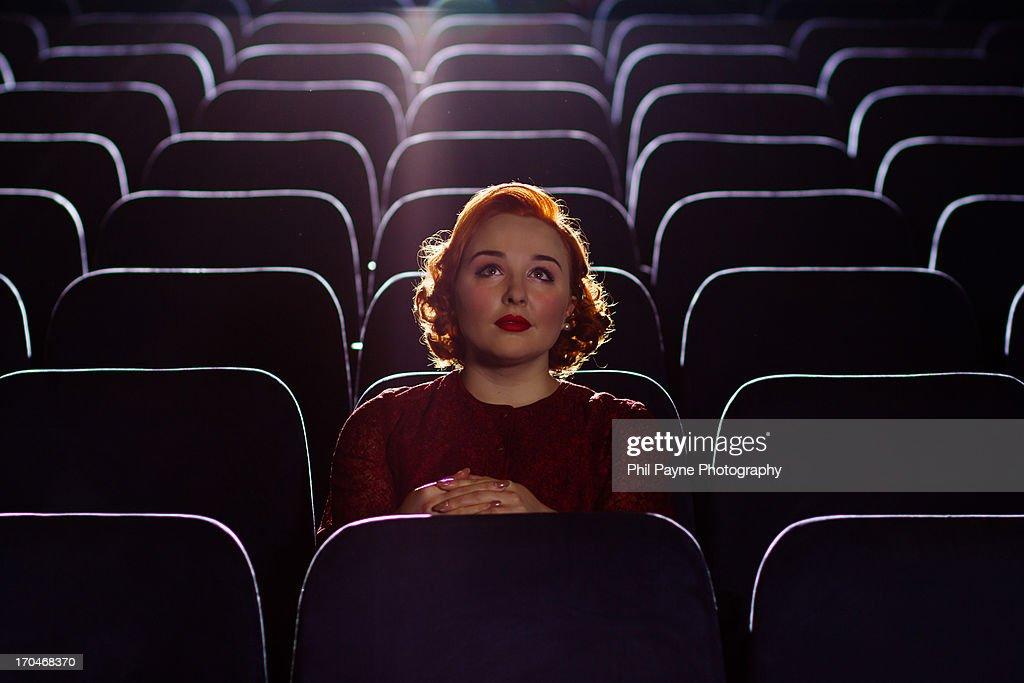 Redhead woman sitting alone in cinema : Stock Photo