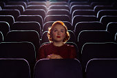 Redhead woman sitting alone in cinema