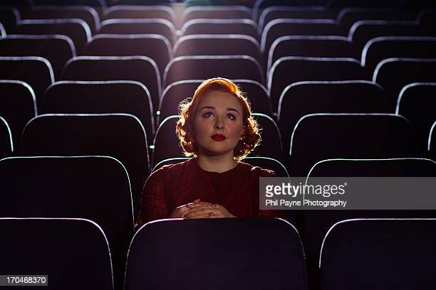 Redhead woman sitting alone in cinema