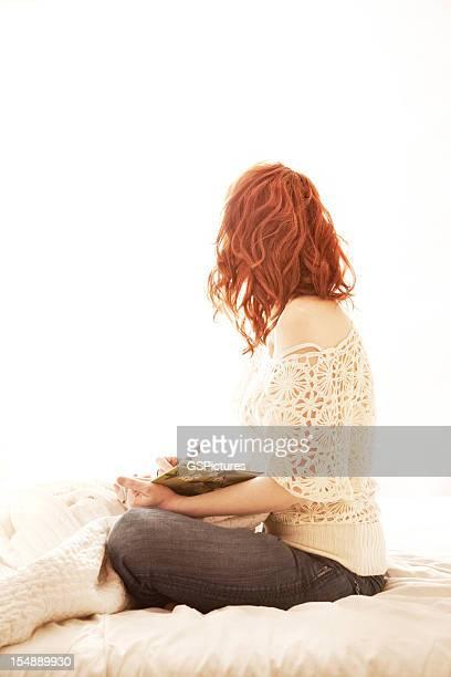Rotes Haar-Frau Schreiben Sitzen im Bett