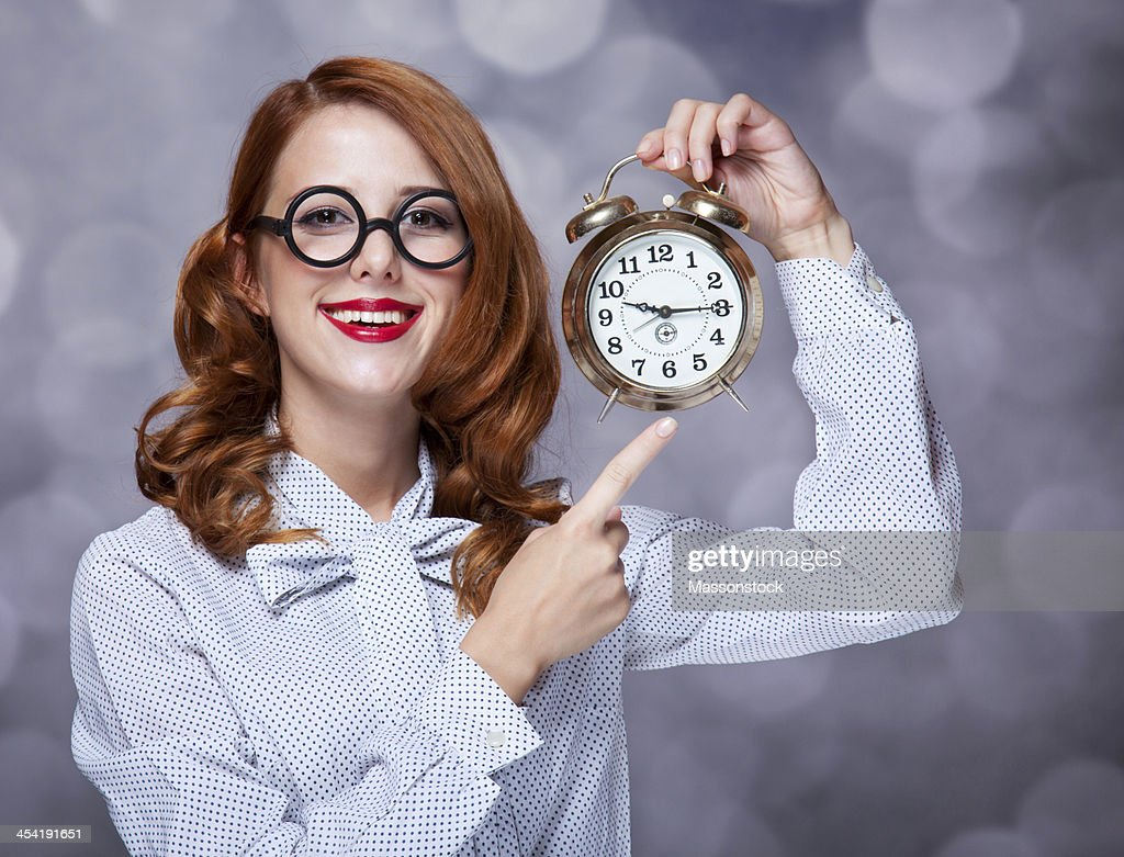 Redhead women with clock. : Stock Photo