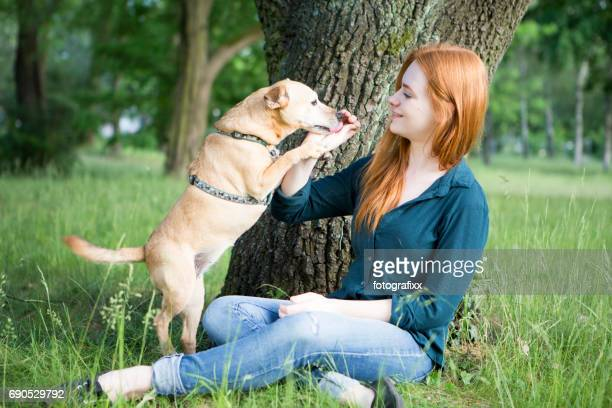 Redhead young woman and her dog have fun outdoors