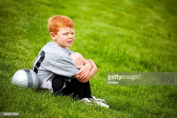 Jugador de fútbol niño pelirroja espera para gire en campo