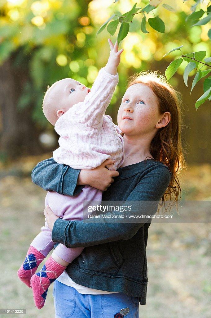 Redheaded girl holding her baby sister