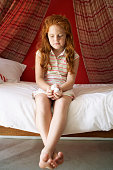 Redheaded Girl Sitting on Bed