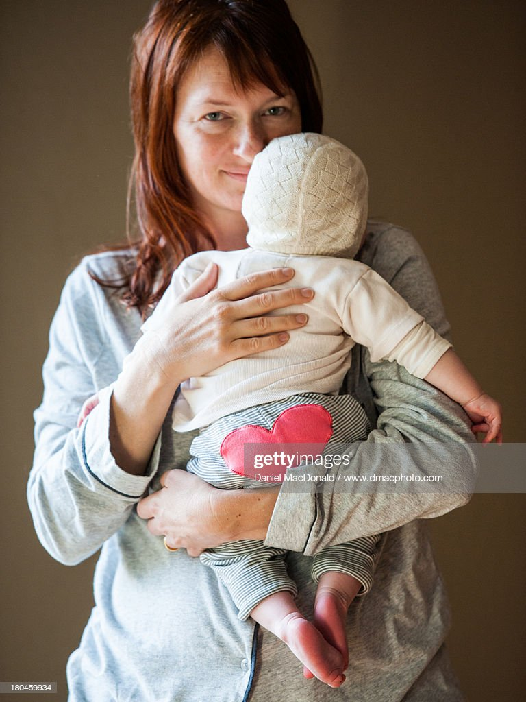 Redheaded mother holding baby with heart on bottom : Stock Photo