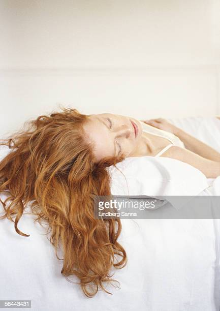 Redheaded woman lying on bed