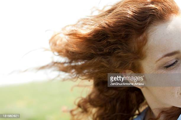 Redheaded woman with hair blowing in wind