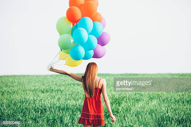 Redheaded woman with red dress holding balloons in grassland