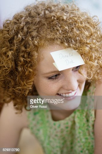 Redheaded woman with sticky notepaper on forehead : Stockfoto