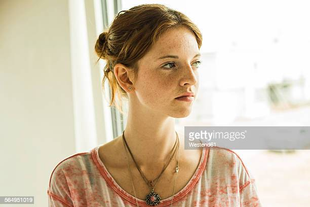 Redheaded young woman looking away