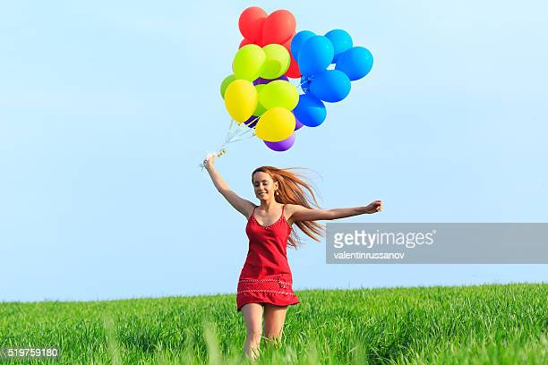 Junge Frau mit roten Haaren mit bunten Luftballons springen