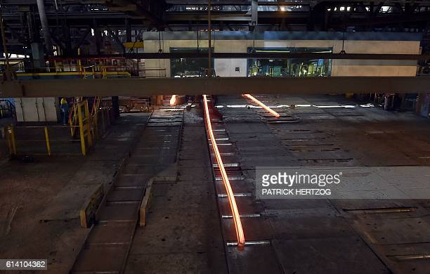 A redhot steel bar exits a furnace at the plant of British Steel in Hayange eastern France on October 12 2016 / AFP / PATRICK HERTZOG
