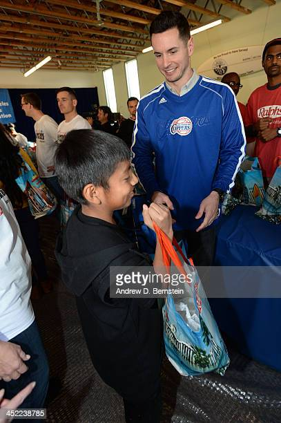 J Redick hands out Thanksgiving dinners during the Teamwork at the Table Thanksgiving Event at the St Joseph Center on November 26 2013 in Venice...