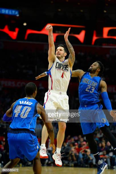 J J Redick of the Los Angeles Clippers attempts a jump shot against Wesley Matthews and Harrison Barnes of the Dallas Mavericks on April 5 2017 at...