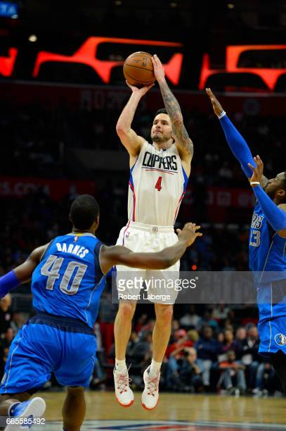 J J Redick of the Los Angeles Clippers attempts a jump shot against Harrison Barnes of the Dallas Mavericks on April 5 2017 at STAPLES Center in Los...