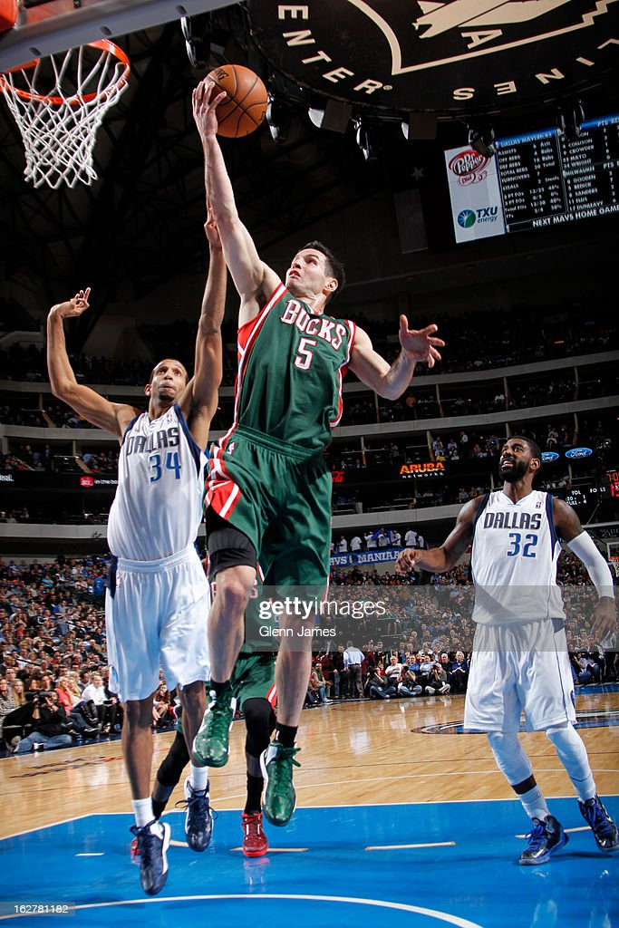 J.J. Redick #5 of the Milwaukee Bucks goes in for the layup against Brandan Wright #34 of the Dallas Mavericks on February 26, 2013 at the American Airlines Center in Dallas, Texas.