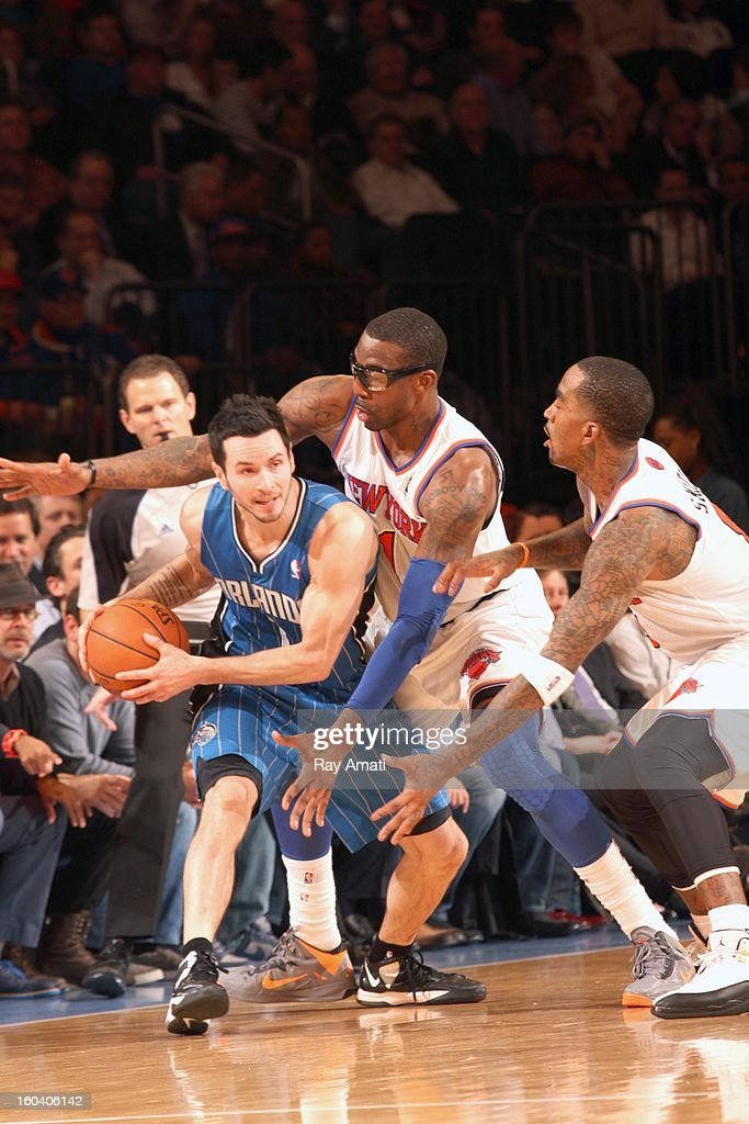 J.J. Redick #7 of the Orlando Magic is defended by Amar'e Stoudemire #1 and J.R. Smith #8 of the New York Knicks on January 30, 2013 at Madison Square Garden in New York City.