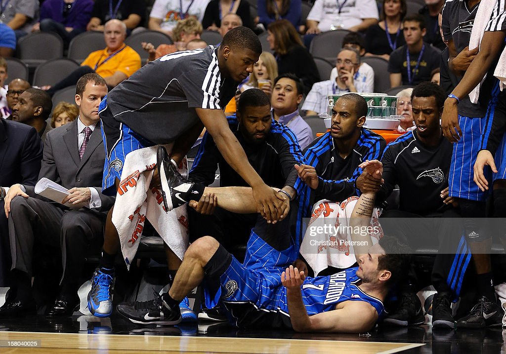 J.J. Redick #7 of the Orlando Magic is helped up by teammates on the bench after being fouled by the Phoenix Suns during the NBA game at US Airways Center on December 9, 2012 in Phoenix, Arizona.