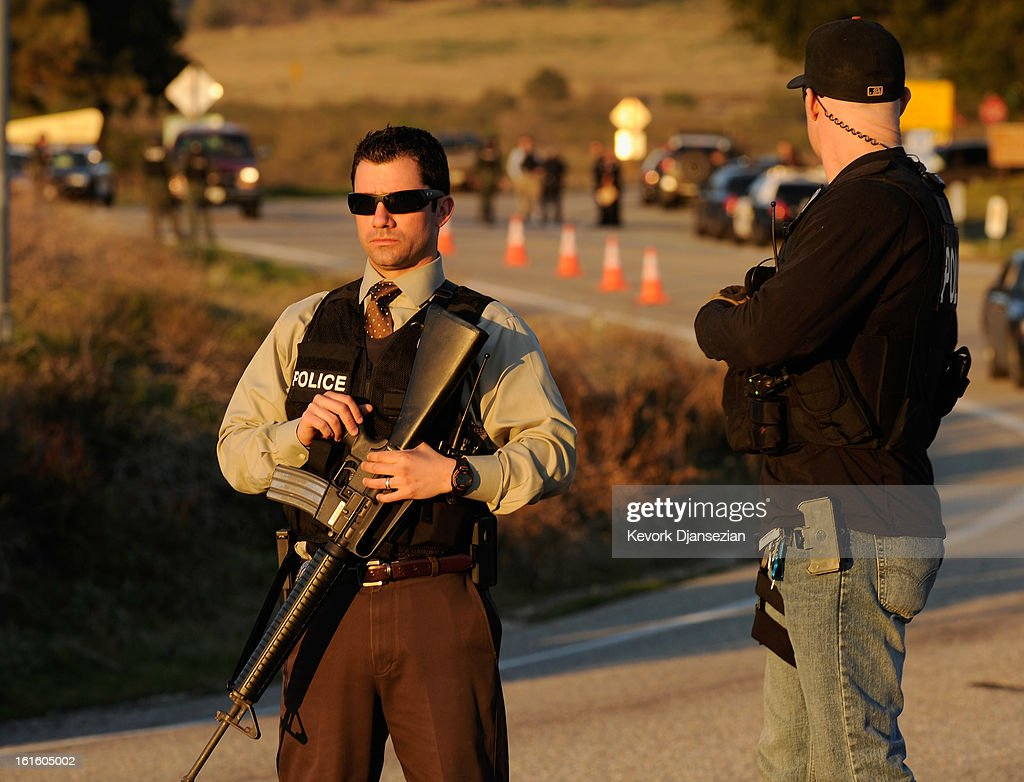 Redlands police officers secure at a blockade during a manhunt for the former Los Angeles Police Department officer Christopher Dorner who is suspected of triple murder on February 12, 2013 in Yucaipa, California. Dorner barricaded himself in a cabin near Big Bear, California and is in a standoff with authorities after shooting two police officers, killing one and wounding the other. Dorner, a former Los Angeles Police Department officer and Navy Reserve veteran, is wanted in connection with the deaths of an Irvine couple and a Riverside police officer.