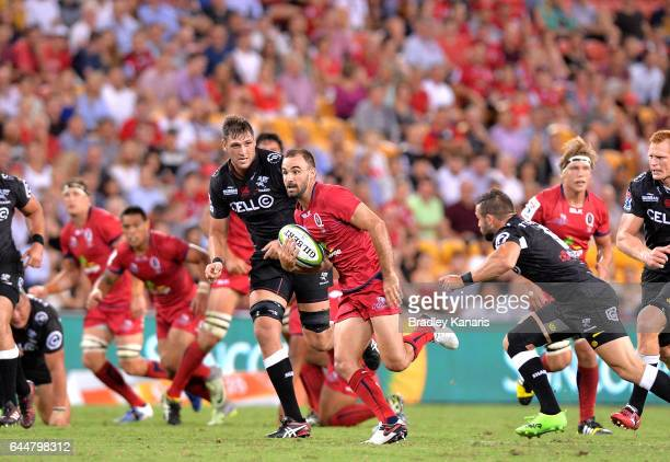Reds player Nick Frisby breaks away from the defence during the round one Super Rugby match between the Reds and the Sharks at Suncorp Stadium on...