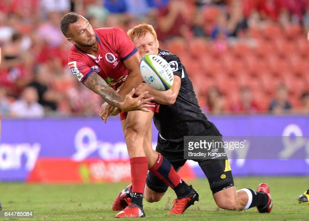 Reds player Quade Cooper gets a ball away during the round one Super Rugby match between the Reds and the Sharks at Suncorp Stadium on February 24...