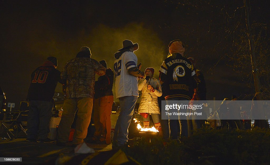 Redskins and Cowboys fans keep warm by a fire while tailgating before a game between the Dallas Cowboys and Washington Redskins at FedEx Field on December 30, 2012 in Landover, Md.