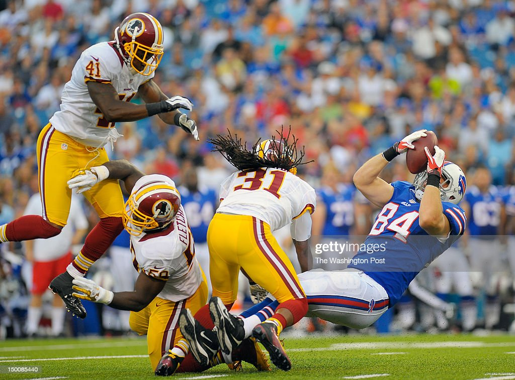 Redskins defenders' Madieu Williams, left London Fletcher, center left, Brandon Meriweather, center, right, plow Bills' receiver Scott Chandler, right, into the ground after a 1st quarter reception as the Washington Redskins play the Buffalo Bills in the first pre-season game at Ralph Wilson Stadium in Orchard Park NY August 9, 2012