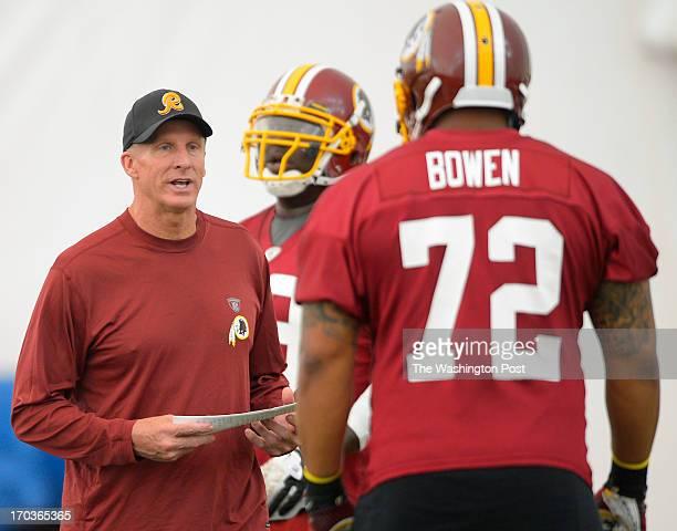 Redskins defensive coordinator Jim Haslett left talks to defensive end Stephen Bowen during the Washington Redskins minicamp held in their indoor...