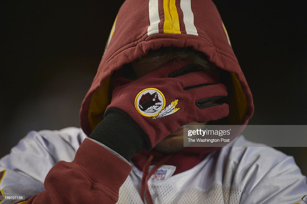 A Redskins fan covers his face after his team loses a first round NFC playoff game against the Seattle Seahawks at FedEx Field on January 6, 2013 in Landover, Md.
