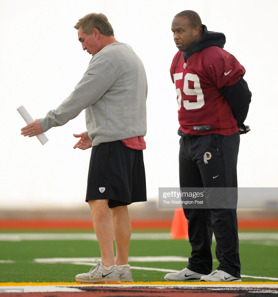 Redskins head coach Mike Shanahan, left, talks with non practicing inside linebacker London Fletcher (59) as the Washington Redskins practice for the upcoming playoff game against the Seattle Seahawks in their indoor practice facility at Redskins Park in Ashburn VA, January 2, 2012 .