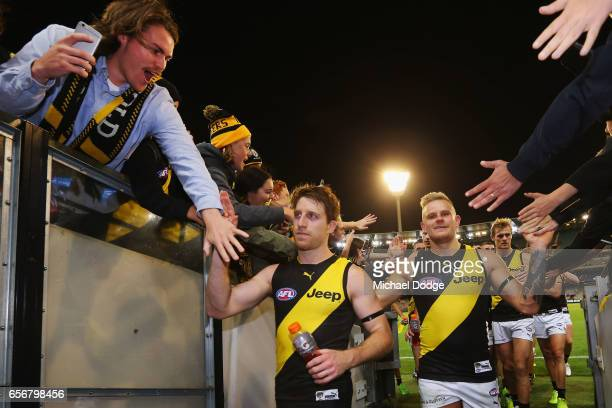 Reece Conca and Brandon Ellis of the Tigers celebrates the win with fans during the round one AFL match between the Carlton Blues and the Richmond...