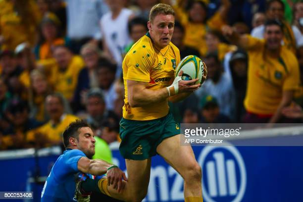 Reece Hodge of Australia beats the diving tackle of Dean Budd to score a try during the international rugby match between Australia and Italy at...