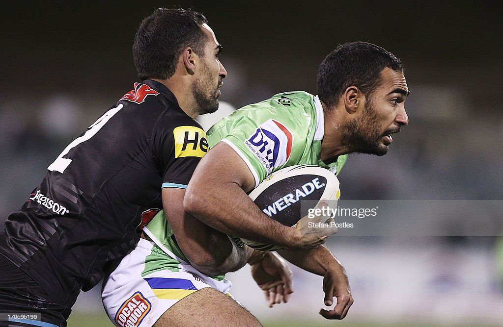Reece Robinson of the Raiders is tackled by brother Travis Robinson of the Panthers during the round 14 NRL match between the Canberra Raiders and the Penrtih Panthers at Canberra Stadium on June 15, 2013 in Canberra, Australia.