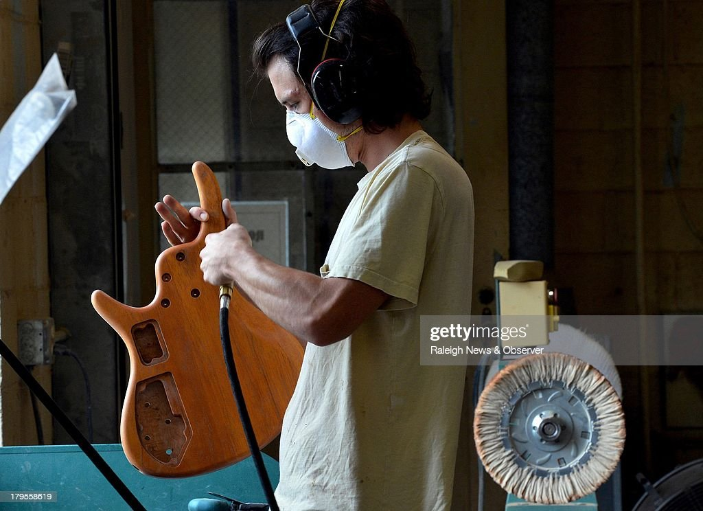 Reed Albach uses compressed air as he gets a guitar body ready for the finishing process at Roscoe Guitars in Greensboro, North Carolina, on Wednesday August 28, 2013.