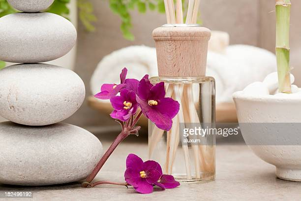 reed diffuser beside african violet flowers