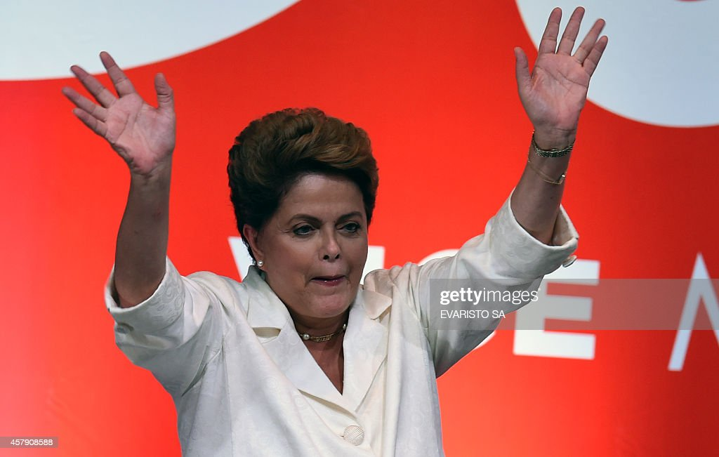 Re-elected Brazilian President <a gi-track='captionPersonalityLinkClicked' href=/galleries/search?phrase=Dilma+Rousseff&family=editorial&specificpeople=1955968 ng-click='$event.stopPropagation()'>Dilma Rousseff</a> waves following her win, in Brasilia on October 26, 2014. Leftist incumbent <a gi-track='captionPersonalityLinkClicked' href=/galleries/search?phrase=Dilma+Rousseff&family=editorial&specificpeople=1955968 ng-click='$event.stopPropagation()'>Dilma Rousseff</a> was re-elected president of Brazil, the country's Supreme Electoral Tribunal said, after a down-to-the-wire race against center-right challenger Aecio Neves. Rousseff, who had 51.45 percent of the vote with 98 percent of ballots counted, was declared the run-off winner. AFP PHOTO / EVARISTO SA