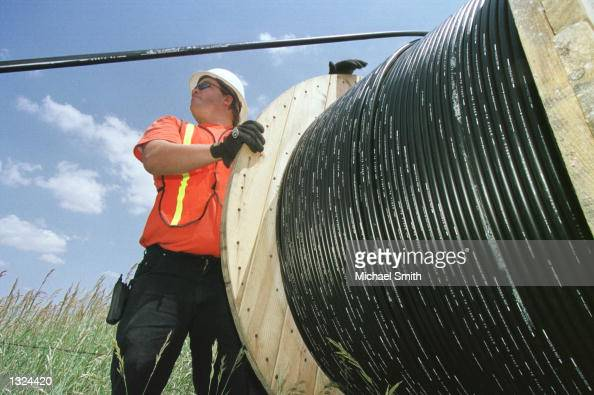 Reeltender Mo Laussie watches fiberoptic cable as he helps install the cable unto telephone poles June 21 2001 in Louisville CO