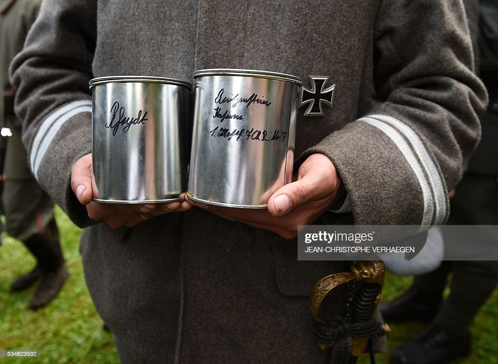 A reenactor dressed as a German soldier holds cans of German soil to lay onto graves ats the German WWI cemetery of Troyon, eastern France, on May 28, 2016, during the 100-year commemoration of WWI's Battle of Verdun. VERHAEGEN