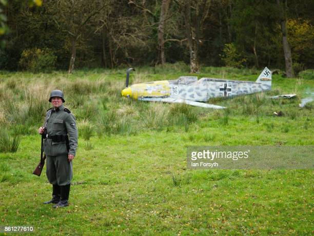 A reenactor dressed as a German soldier stands guard at the crashsite of a German Messerschmitt 109 fighter during a demonstration at the North...