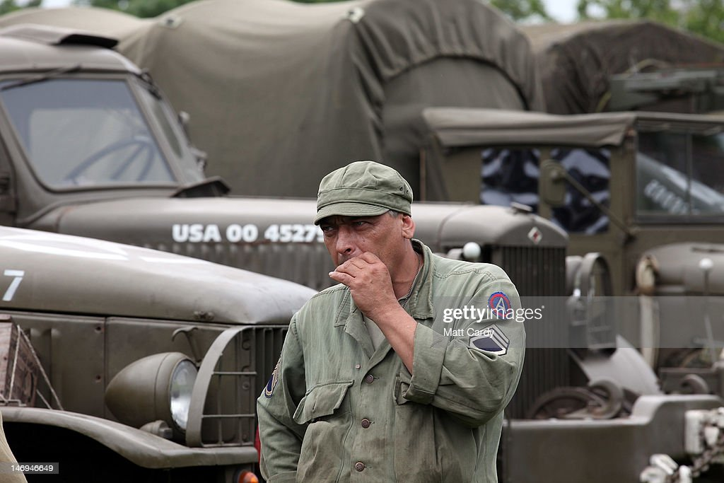 A re-enactor dressed as a Second World War American soldier smokes a cigarette in front of vehicles being displayed as part of the two-day Maiden Newton At War 1940s re-enactment weekend in Maiden Newton on June 23, 2012 near Dorchester, England. The quiet Dorset village of Newton Maiden was seen as a strategic hub during the Second World War and was heavily fortified against a threatened German invasion. It later saw hundreds of American servicemen quartered in the area before the D Day landings. To celebrate the village's wartime past, the biennial event, which started in 2008, has grown into one of the biggest re-enactments in the country and this year featured one of the largest convoys of Second World War vehicles seen in Dorset since D Day in 1944.