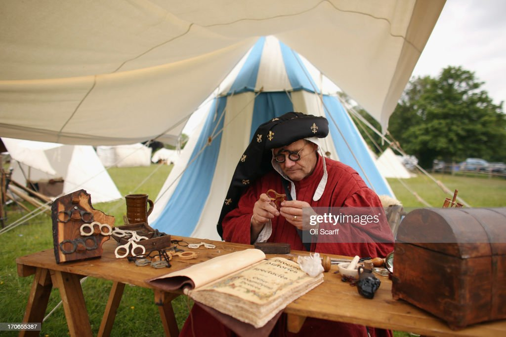 A re-enactor in period costume fashions spectacles in a medieval encampment at Eltham Palace on June 16, 2013 in Eltham, England. The 'Grand Medieval Joust' event at Eltham Palace, an English Heritage property which was the childhood home of King Henry VIII, aims to give a great insight into life at the palace during the medieval period.