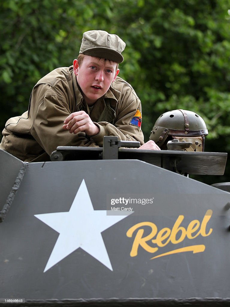 A re-enactor looks as a convoy of Second World War vehicles prepare to leave the village as part of the two-day Maiden Newton At War 1940s re-enactment weekend in Maiden Newton on June 23, 2012 near Dorchester, England. The quiet Dorset village of Newton Maiden was seen as a strategic hub during the Second World War and was heavily fortified against a threatened German invasion. It later saw hundreds of American servicemen quartered in the area before the D Day landings. To celebrate the village's wartime past, the biennial event, which started in 2008, has grown into one of the biggest re-enactments in the country and this year featured one of the largest convoys of Second World War vehicles seen in Dorset since D Day in 1944.