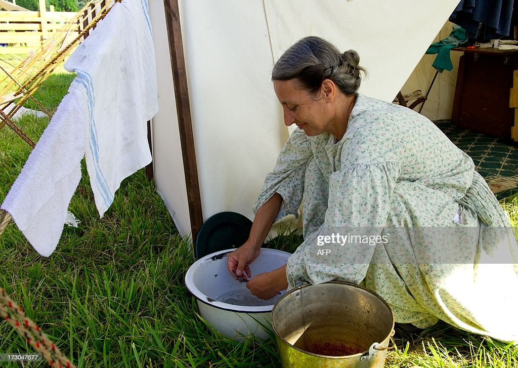 A re-enactor washes breakfast dishes in the Confederate camp on July 5, 2013 at the 150th Gettysburg celebration and re-enactments in Gettysburg, Pennsylvania. The Battle of Gettysburg is underway for the second time in a week and tourists turned out in droves even though the outcome of the Civil War's pivotal encounter has been known for 150 years. This re-enactment was held by the Gettysburg Anniversary Committee, the group which has held such events for roughly two decades. This event appeared to draw bigger crowds on the July 4th holiday than the re-enactments held last weekend by the Blue-Gray Alliance. AFP PHOTO / Karen BLEIER